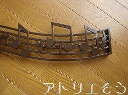 アルミ製の五線譜に音符で音楽を奏でた室内開口部飾りの写真