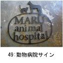 猫と犬のモチーフを組み合わせたロートアイアン風のステンレス製動物病院の看板の写真