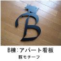 イニシャルBと豚のモチーフを組み合わせたロートアイアン風ステンレス製マンションB棟の看板の写真