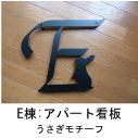 イニシャルEとうさぎのモチーフを組み合わせたロートアイアン風ステンレス製マンションE棟の看板の写真